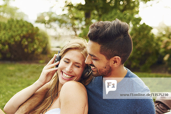 Junge Frau und Mann hören Kopfhörermusik im Park