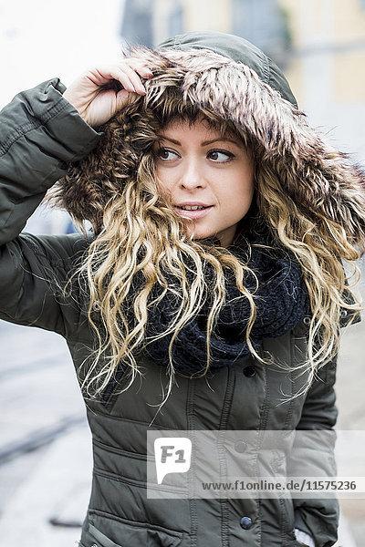 Portrait of woman wearing fur trimmed hooded coat