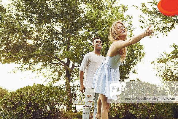 Young woman and man throwing flying disc in park