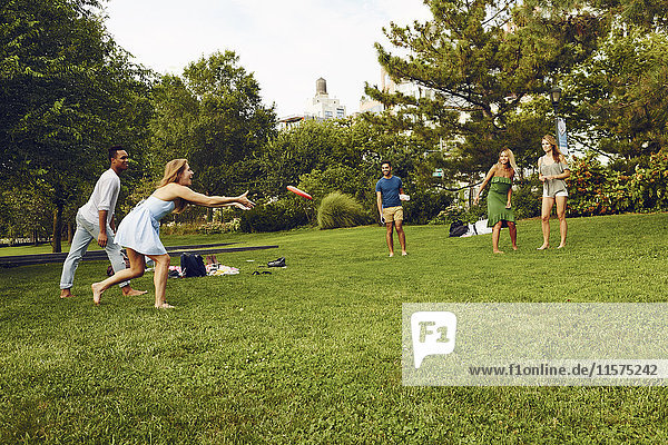 Five adult friends playing with flying disc in park