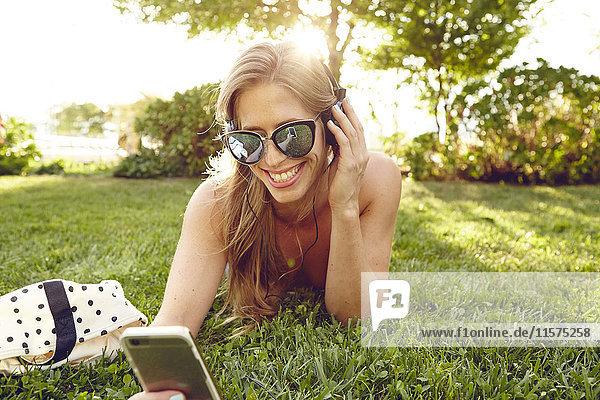 Junge Frau liegt im sonnenbeschienenen Park und hört Smartphone-Musik
