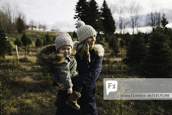 Mother and baby girl in Christmas tree farm  Cobourg  Ontario  Canada