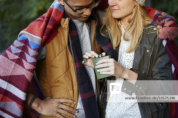 Cropped shot of couple wrapped in blanket  opening hip flask in park
