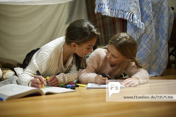 Two sisters lying on bedroom floor drawing in sketchbooks