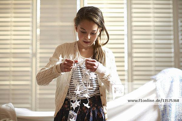 Girl untangling star shape decorative lights