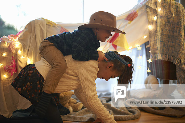 Boy in cowboy hat getting piggyback ride from sister