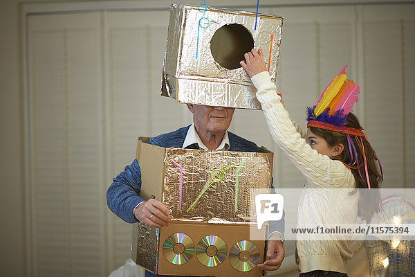 Girl in feather headdress putting robot costume onto grandfather