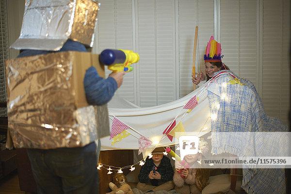 Senior man in robot costume having dress up play fight with grandchildren