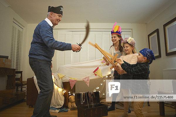 Senior man in pirate hat having sword fight with dressed up grandchildren