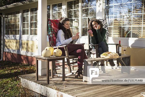 Zwei junge Freundinnen beim Kartenspiel auf der Terrasse