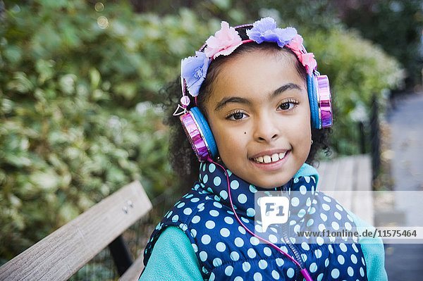 Girl wearing headphones looking at camera smiling