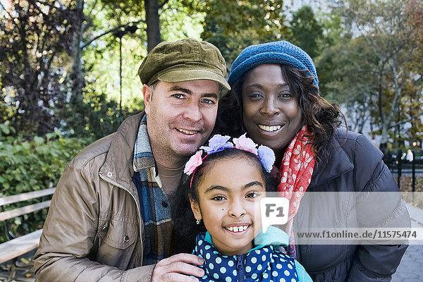 Familie im Park schaut lächelnd in die Kamera