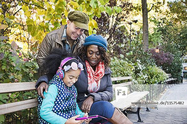 Familie im Park auf Bank mit digitalem Tablett