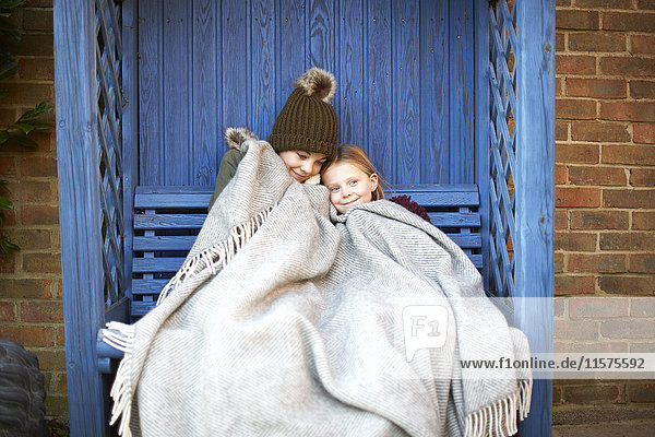 Siblings wrapped in blanket resting on arbour bench