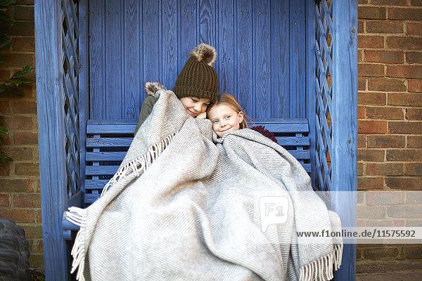 In eine Decke gewickelte Geschwister ruhen auf der Laube