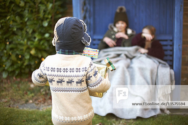 Siblings playing and resting on arbour bench