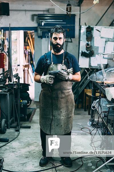 Porträt eines männlichen Metallarbeiters in Schürze  Schmiedewerkstatt