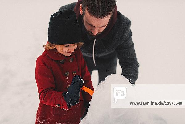 Vater und Tochter beim Schneemannbauen