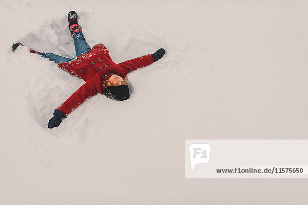 Mädchen auf Schnee liegend