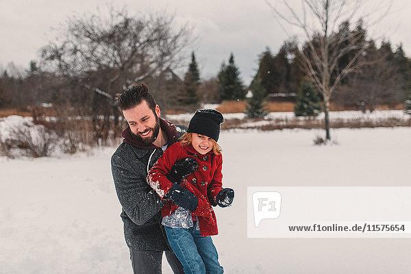 Vater und Tochter spielen im Schnee