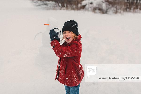 Mädchen macht sich bereit  Schneeball zu werfen