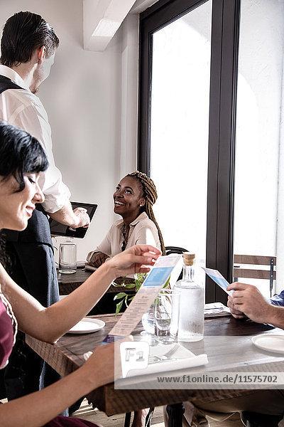 Kellner serviert Speisen im Restaurant  Kellner mit digitalem Tablett
