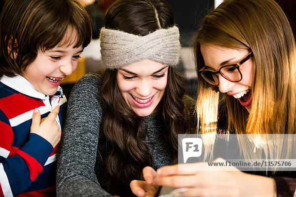 Two young women and boy looking and laughing at smartphone in cafe
