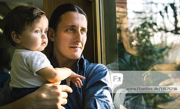 Reifer Mann und kleiner Sohn schauen durchs Fenster