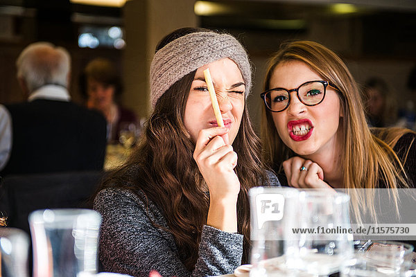 Portrait of two young women pulling faces in cafe