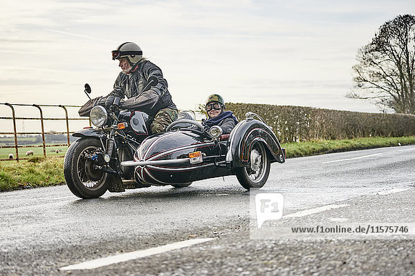 Senior man and grandson riding motorcycle and sidecar along rural road