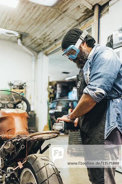 Mature man  working on motorcycle in garage