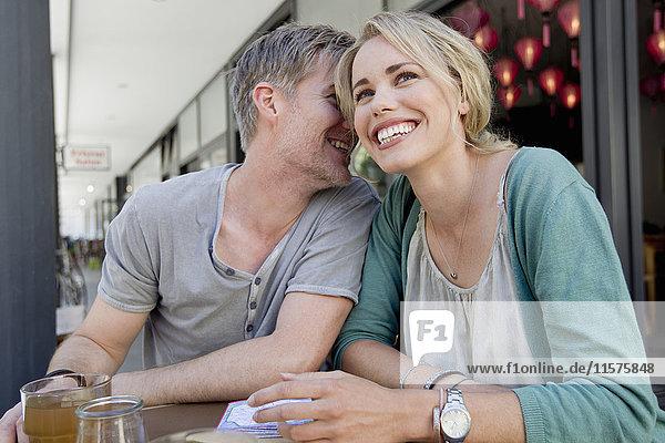 Couple whispering at city sidewalk cafe