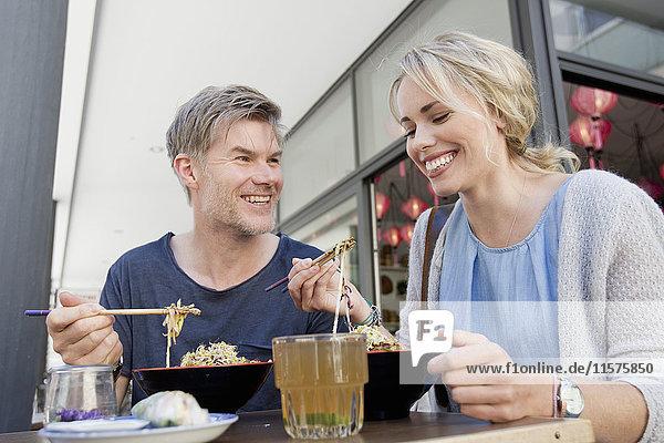 Couple eating noodles at city sidewalk cafe Couple eating noodles at city sidewalk cafe