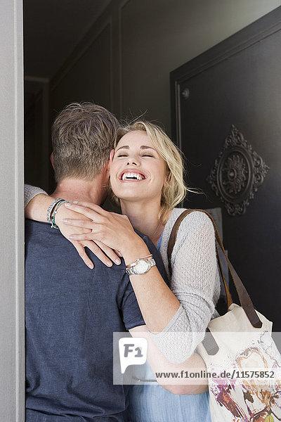 Couple hugging in doorway