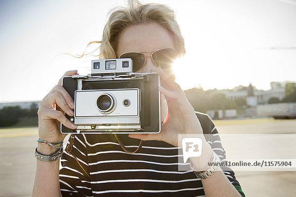 Mittlere erwachsene Frau  die mit einer Oldtimer-Kamera fotografiert