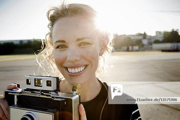 Porträt einer mittleren erwachsenen Frau im Sonnenlicht mit Vintage-Kamera