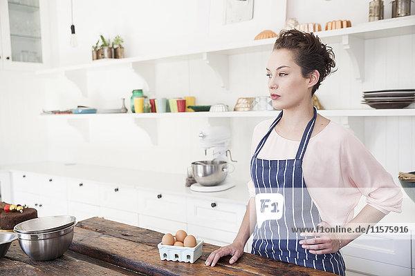 Junge Frau steht mit einem Karton Eier an der Küchentheke