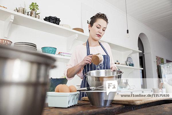 Junge Frau gießt Mehl in eine Schüssel an der Küchentheke