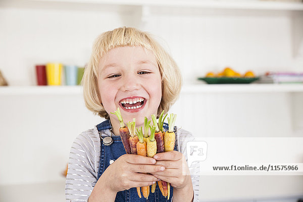Portrait of cute girl in kitchen holding bunch of colourful carrots