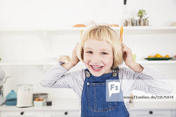 Porträt eines süßen Mädchens in der Küche  das Karotten an den Ohren hält