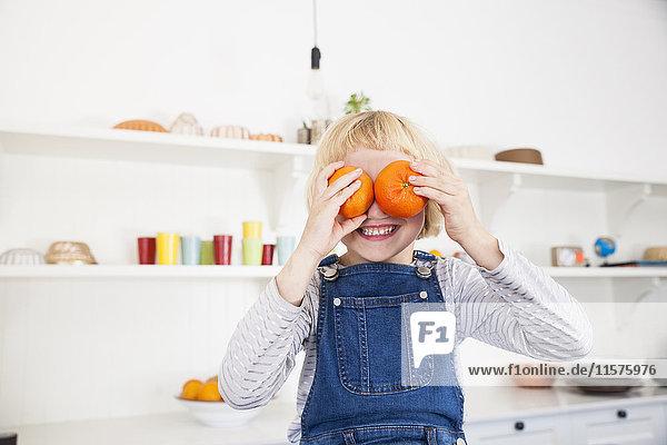 Porträt eines süßen Mädchens in der Küche  das Orangen an ihre Augen hält