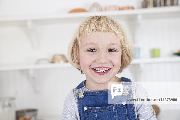 Porträt eines glücklichen  süßen Mädchens mit blondem Bob in der Küche