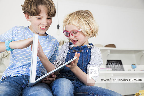 Mädchen spielt Streit mit dem Bruder über ein Märchenbuch auf dem Küchentisch