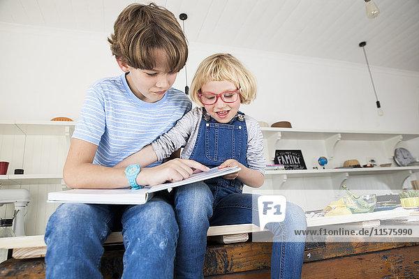Mädchen schnappt sich Märchenbuch vom Bruder auf der Küchentheke