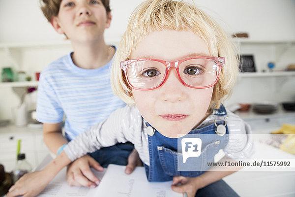 Bildnis eines süßen Mädchens mit Brille und Bruder in der Küche