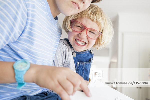 Mädchen zieht beim Lesen mit Bruder in der Küche das Gesicht