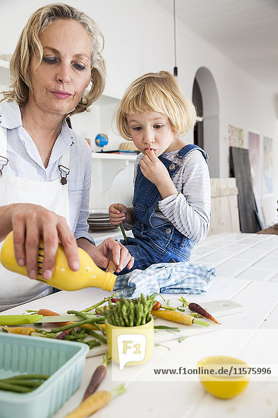 Mature woman and daughter preparing asparagus at kitchen table