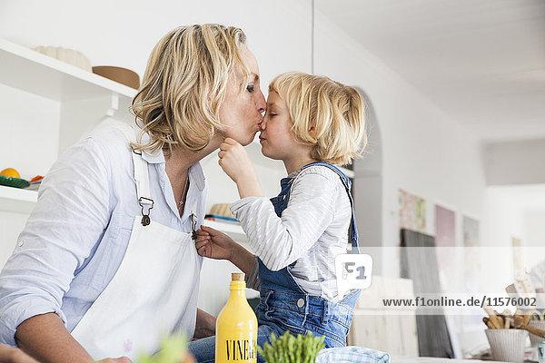 Reife Frau küsst Tochter am Küchentisch