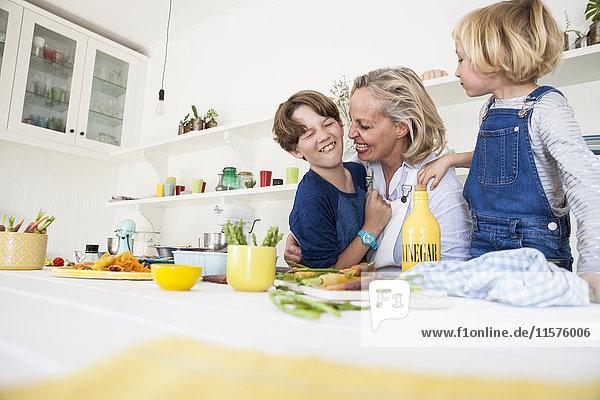 Reife Frau kitzelt Sohn am Küchentisch