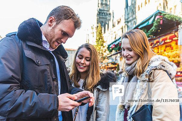Junger Mann und Freundinnen schauen sich auf dem Weihnachtsmarkt ein Smartphone an